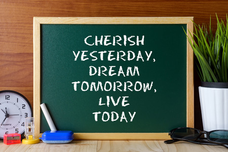 cherish: Word quote CHERISH YESTERDAY,DREAM TOMORROW,LIVE TODAY written on green chalk board on wooden table. Stock Photo