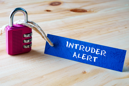 intruder: Words INTRUDER ALERT written on tag label tied with a padlock.
