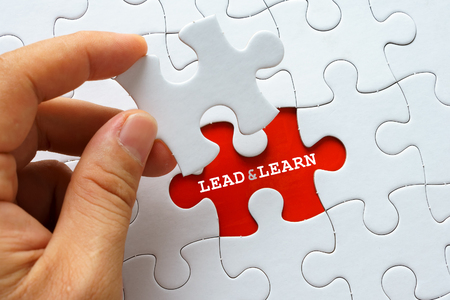 learn and lead: White puzzle with word LEAD AND LEARN.