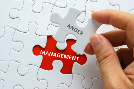 anger management: Hand holding piece of blank jigsaw puzzle with word ANGER MANAGEMENT. Stock Photo