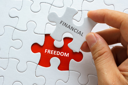 Hand holding piece of blank jigsaw puzzle with word FINANCIAL FREEDOM.