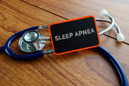 somnambulism: Medical concept.Word SLEEP APNEA with stethoscope on wooden table. Stock Photo