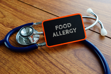 food allergy: Medical concept.Word FOOD ALLERGY with stethoscope on wooden table. Stock Photo