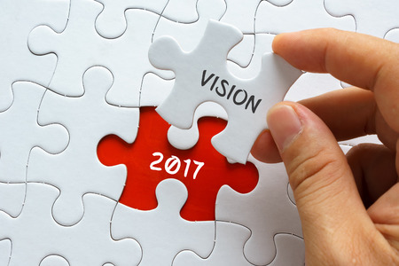initiatives: Hand holding jigsaw puzzle with word VISION 2017. Stock Photo