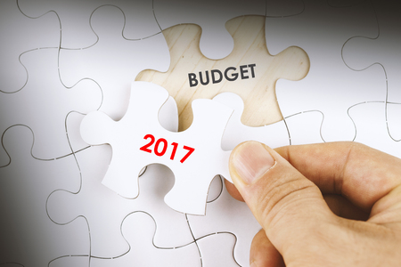 initiatives: Hand holding a piece of jigsaw puzzle with word BUDGET 2017. Stock Photo