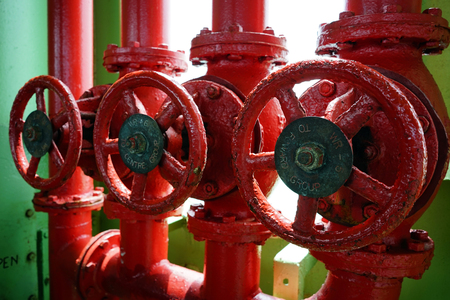 Old valves and pipes painted in vivid bright red color.