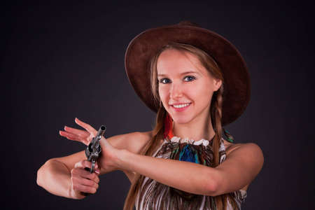 sexy cowboy: The American Indian girl in a cowboys hat holds a pistol