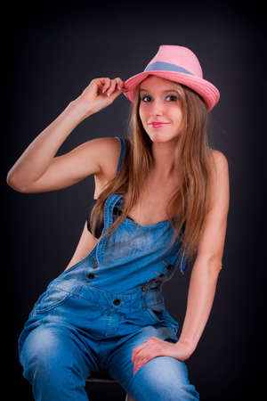 pink hat: Pretty girl in pink hat and jeans overalls Stock Photo