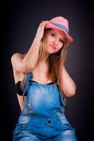 Pretty girl in pink hat and jeans overalls photo