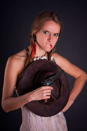 trendy girl: The American Indian girl with a cowboys hat holds a pistol