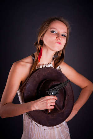 The American Indian girl with a cowboys hat holds a pistol photo