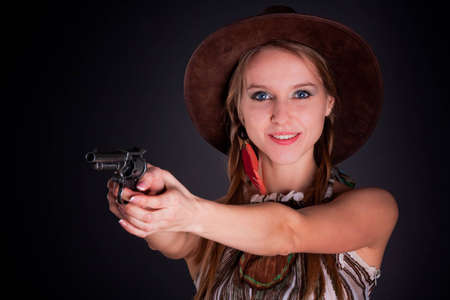 The American Indian girl in a cowboys hat holds a pistol photo