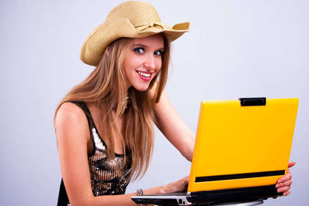 Attractive girl in a straw hat wth a yellow laptop Zdjęcie Seryjne