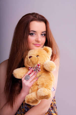 Beautiful longhair girl is holding the teddy bear photo