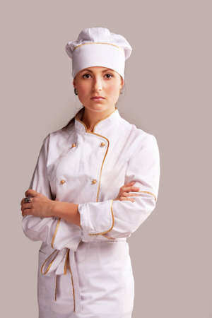 Young woman in white chef dress with hat photo