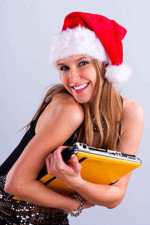 Pretty girl in Santa hat holding a laptop photo