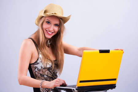 Attractive girl in a straw hat wth a yellow laptop photo