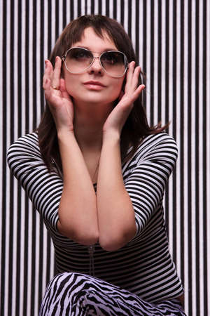 Cute girl in a striped clothes and sunglasses on the striped background Stock Photo - 9157940