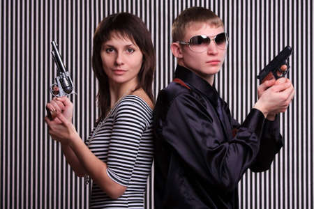 Young couple holding guns over stripe background photo