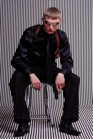 Serious man with a gun against striped background photo