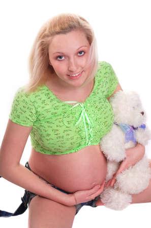Cute pregnant girl sitting with teddy bear Banco de Imagens