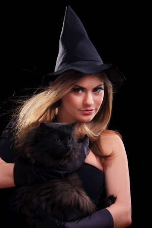 Beautiful girl dressed as a witch holding cat photo