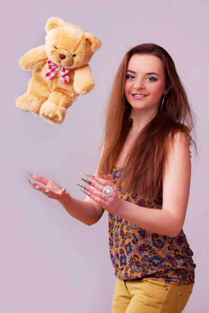 Beautiful young longhair brunette playing with bear photo
