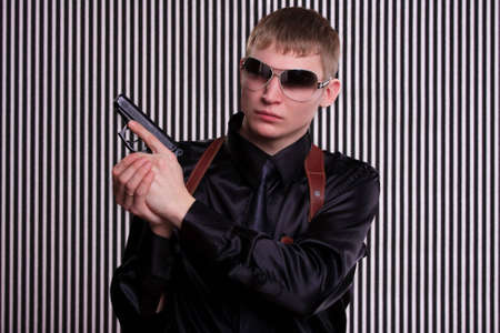 Serious man with a gun standing against striped background photo