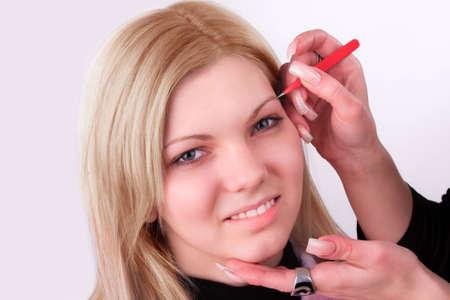 Stylist is applying eyebrow tweezers for young girl photo