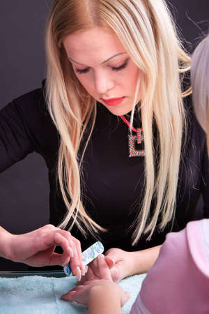 Manicure process. Pro at work with her client. photo