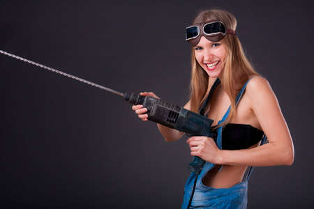 Girl with a drill in building overalls photo