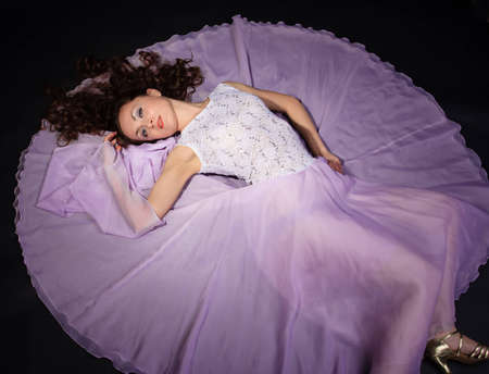 Attractive woman lying on the floor in liliac dress Stock Photo - 9544210