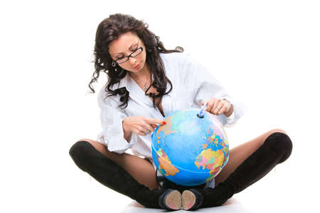 Beautiful woman sits and holds a globe isolated on white background photo