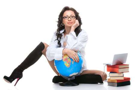 An isolated shot of a woman with laptop, globe and a stack of books photo