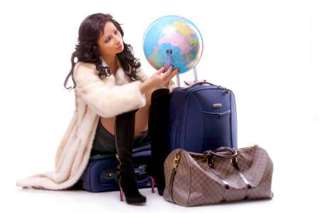 Tourist girl sitting on a suitcase with a globe in her hands Zdjęcie Seryjne