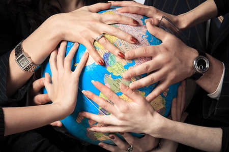 touching hands: Several different people hold the globe in their hands