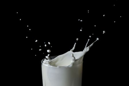 Abstract milk splash against black background Stock Photo - 5367550