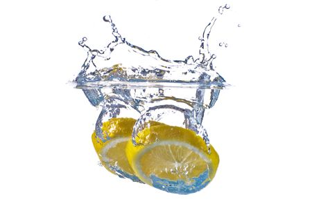 Closeup abstract yellow lemon splashing in clear blue water - isolated against white background. photo