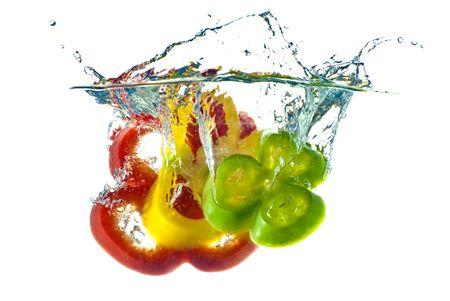 ensalada de verduras: Rojo, amarillo y verde abstracción pimienta chapoteando en agua azul claro - aislado sobre fondo blanco.
