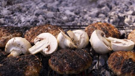 Beef BBQ Cooking of burger meat and mushroom. Iron barbeque grill pan with fire and food. Hamburgers outdoors barbecuing on coals. Closeup beef for burgers on cast iron grill. Juicy fat food grilled. Stock Photo