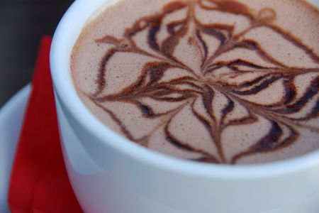 A cup of fresh hot chocolate with a design..