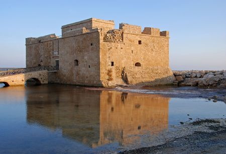 Paphos castle in Cyprus during sunset reflected on water