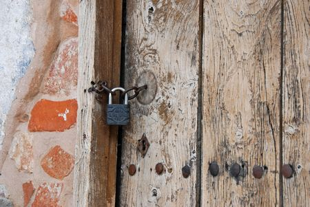 entranceway: Old wooden church door with key lock and a brick wall Stock Photo