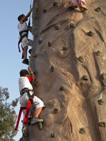 Friends are climbing to reach the top on a playground photo