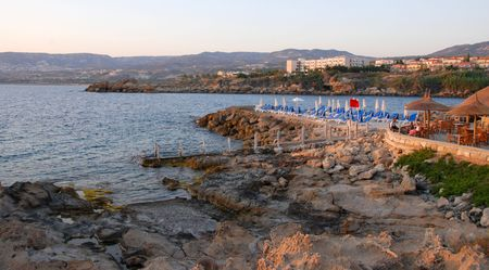 Rocky beach with people relaxing on a beach Pavilion.      photo
