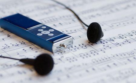 letras musicales: Reproductor de MP3 y auriculares en una hoja de m�sica de fondo
