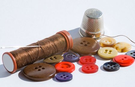 Sewing threads and colorful buttons isolated on white photo