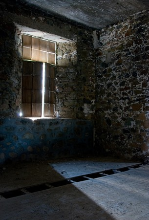 Empty room with sunlight entering through the broken window. Stock Photo