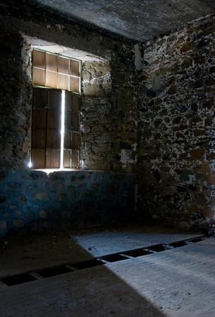 Empty room with sunlight entering through the broken window. Stock Photo