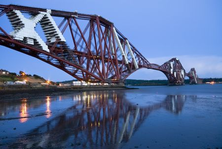 The world-famous Forth Rail Bridge at sunset. Repairing works are taking place on the bridge Stock Photo